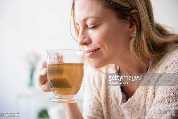 caucasian woman smelling cup of tea - hot tea stock pictures, royalty-free photos & images