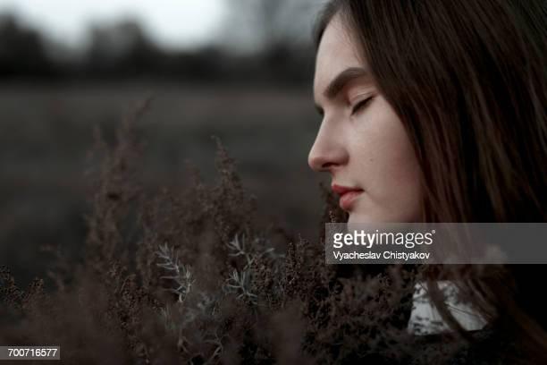 Caucasian woman smelling foliage