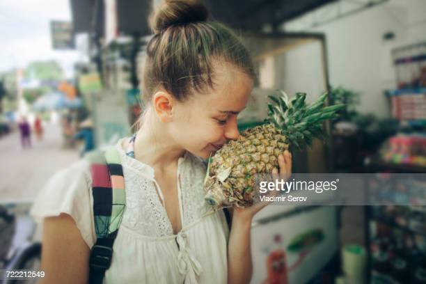 caucasian woman smelling pineapple at market - tropische frucht stock-fotos und bilder