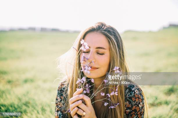 caucasian woman smelling some flowers in rural field, lleida, spain - nature stock pictures, royalty-free photos & images