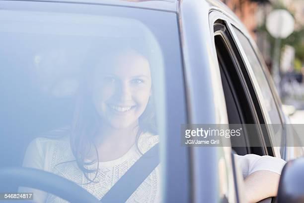 Caucasian woman smiling in car