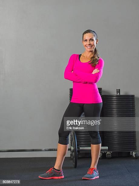 caucasian woman smiling in gym - mujeres de mediana edad fotografías e imágenes de stock