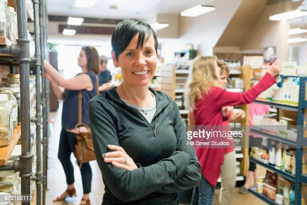 caucasian woman smiling in nutrition store - health food shop stock pictures, royalty-free photos & images