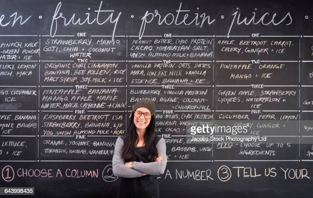 caucasian woman smiling near chalkboard wall in cafe - menu stock pictures, royalty-free photos & images