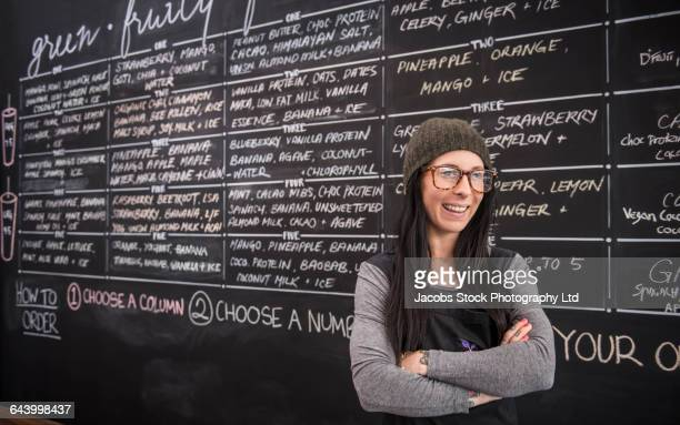 Caucasian woman smiling near chalkboard wall in cafe