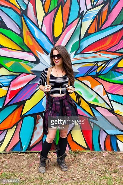 Caucasian woman smiling near multicolor mural