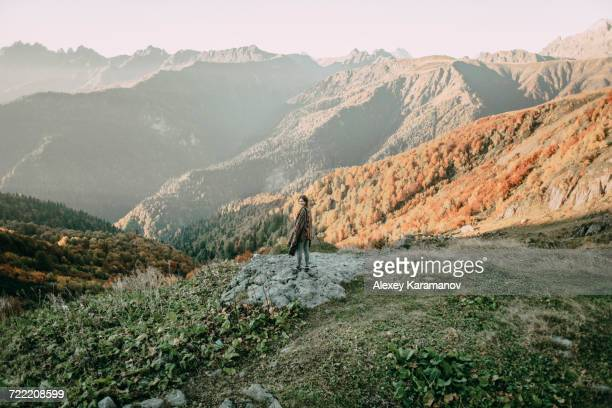 Caucasian woman smiling on mountain overlooking valley