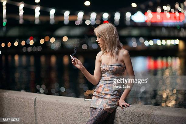 caucasian woman smoking cigarette on urban bridge - beautiful women smoking cigarettes stock photos and pictures
