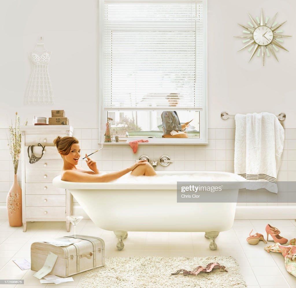 Caucasian woman smoking in bath : Stock Photo