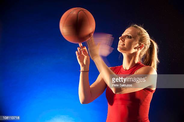 Caucasian woman spinning basketball