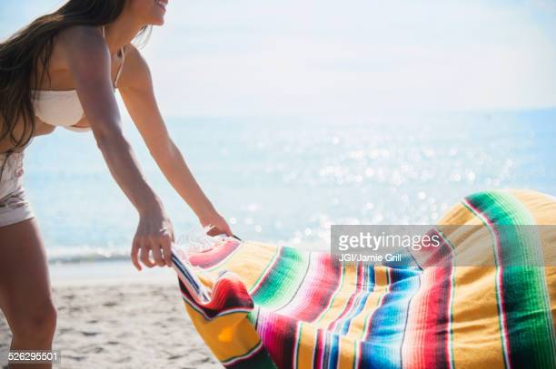 Caucasian woman spreading blanket on beach