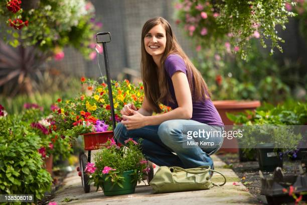 caucasian woman squatting with flowers in plant nursery - toy wagon stock photos and pictures