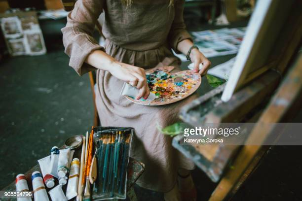 Caucasian woman squeezing paint onto palette