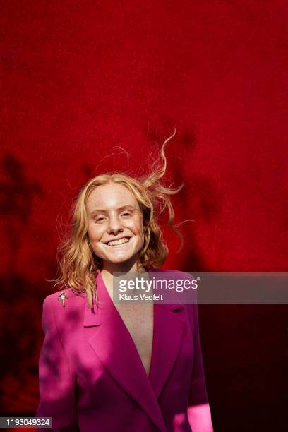 caucasian woman standing against red wall - blazer jacket stock pictures, royalty-free photos & images