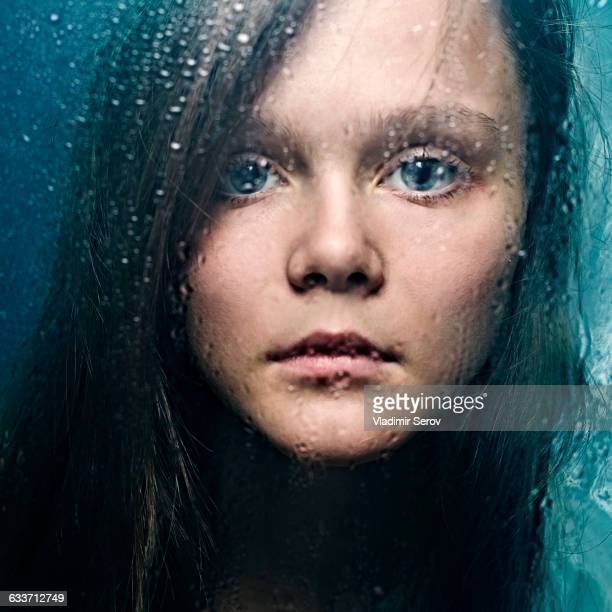 Caucasian woman standing at wet glass