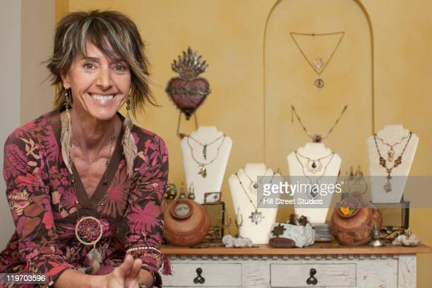 Caucasian woman standing by jewelry display