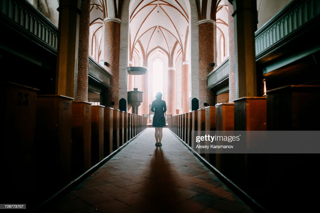 Caucasian woman standing in aisle of church : Stock Photo