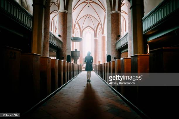 caucasian woman standing in aisle of church - kirche stock-fotos und bilder