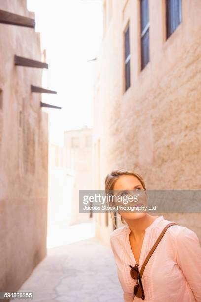 Caucasian woman standing in alley