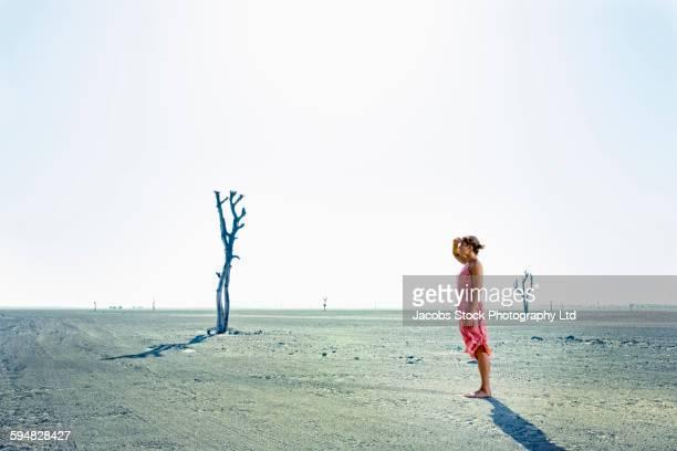Caucasian woman standing in desert