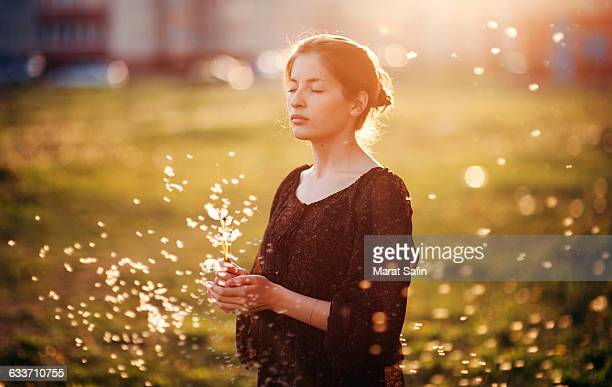 caucasian woman standing in field with blowing dandelion seeds - solo adulti foto e immagini stock
