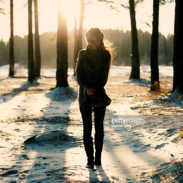 Caucasian woman standing in snowy forest