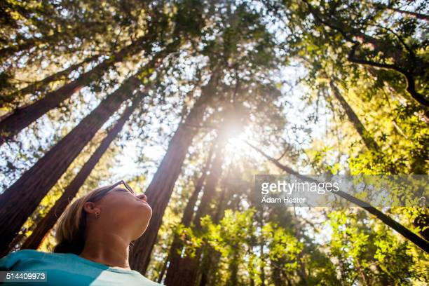 Caucasian woman standing in sunny forest