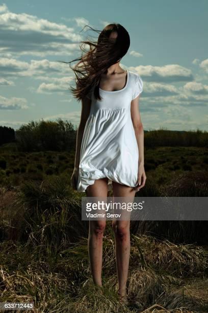Caucasian woman standing in windy field