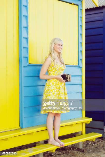 Caucasian woman standing near colorful beach hut