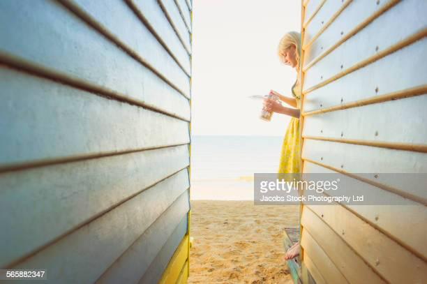 Caucasian woman standing near colorful beach hut