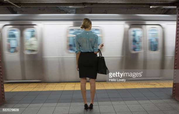 caucasian woman standing near passing subway in train station - new york city subway stock pictures, royalty-free photos & images