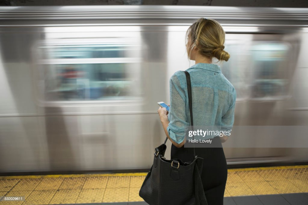 Caucasian woman standing near passing subway in train station : Stock Photo