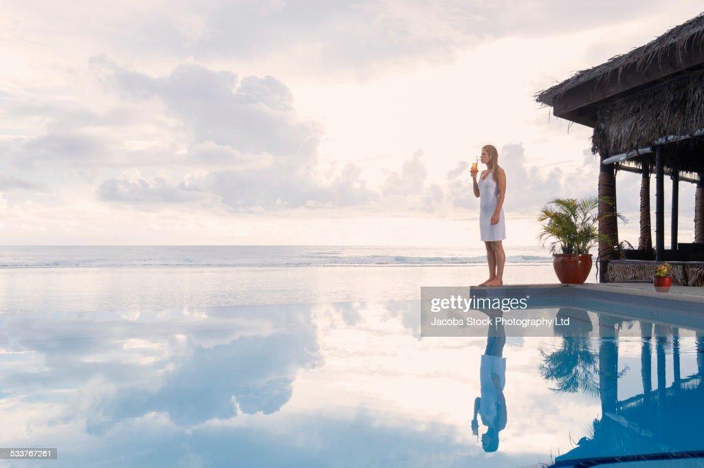 Caucasian woman standing near swimming pool : Foto stock