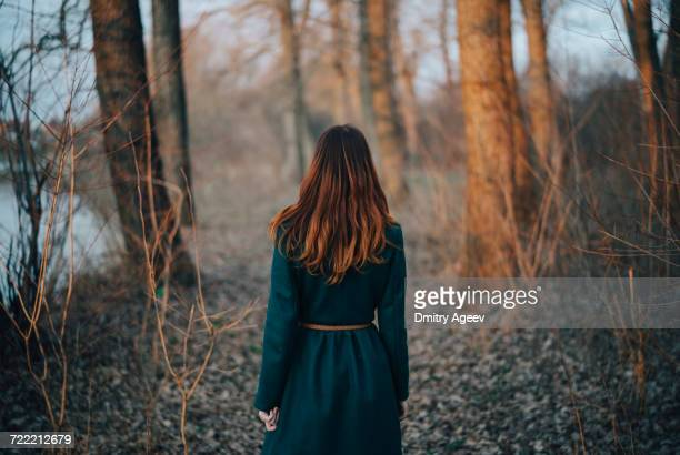 Caucasian woman standing near trees and river