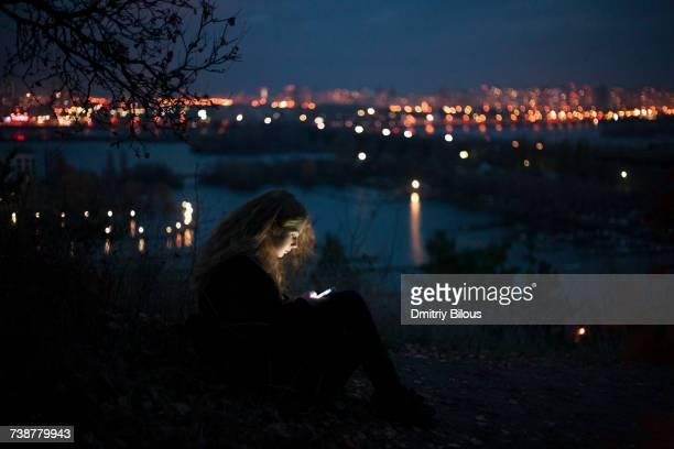 Caucasian woman standing near urban waterfront at night
