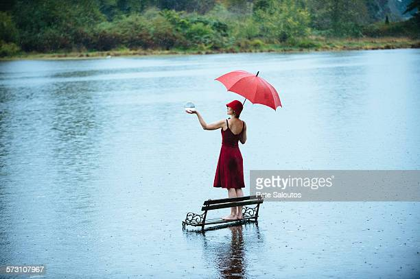 Caucasian woman standing on bench in flood