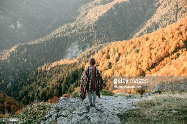 Caucasian woman standing on mountain overlooking valley