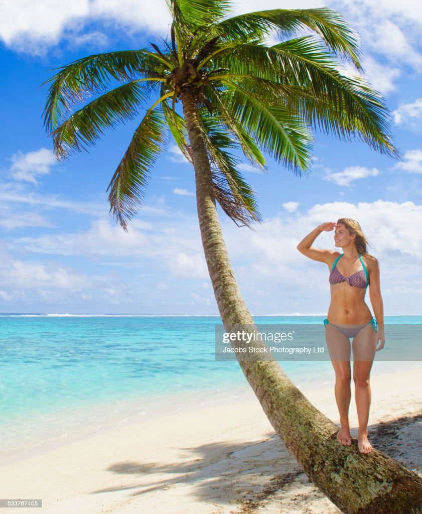 Caucasian woman standing on palm tree on tropical beach : Foto stock