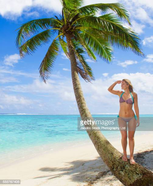 Caucasian woman standing on palm tree on tropical beach