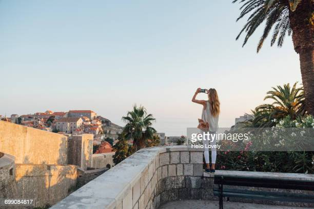 caucasian woman standing on park wall photographing cityscape - photographing stock pictures, royalty-free photos & images