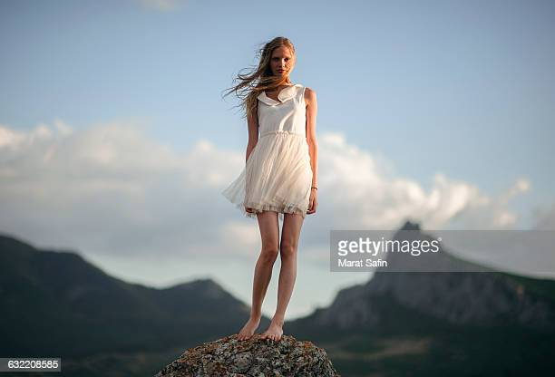 caucasian woman standing on remote hilltop - blue dress stock pictures, royalty-free photos & images