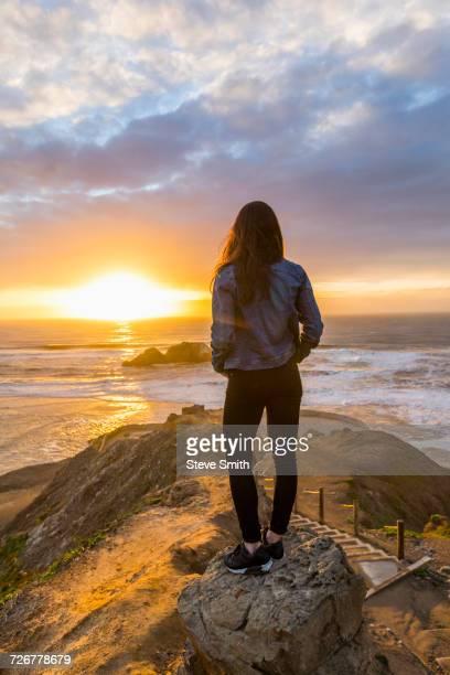 caucasian woman standing on rock near ocean at sunset - femme brune de dos photos et images de collection