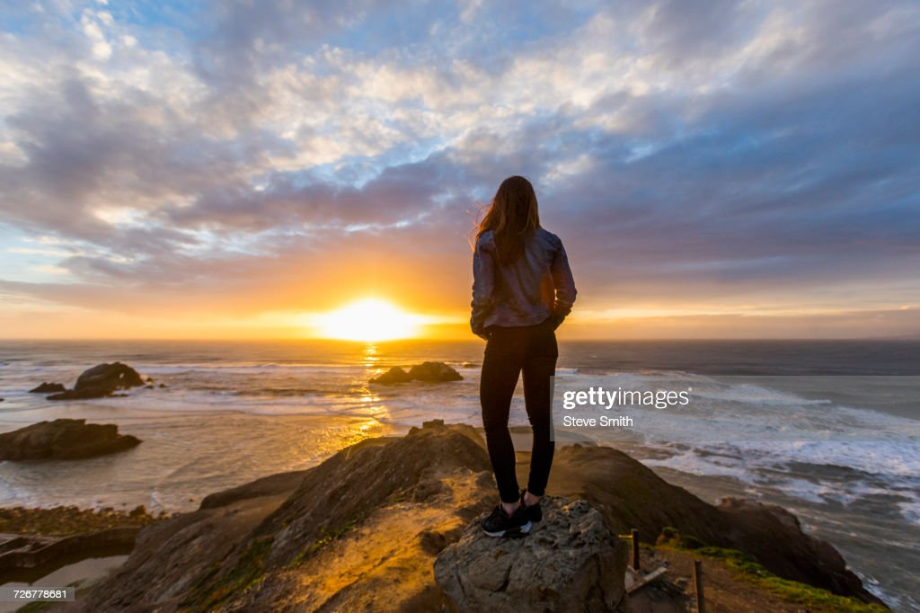 Caucasian woman standing on rock near ocean at sunset : Stock Photo