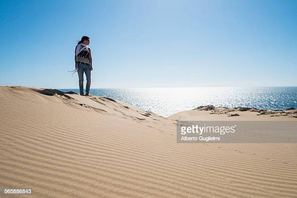 Caucasian woman standing on sand dune near ocean