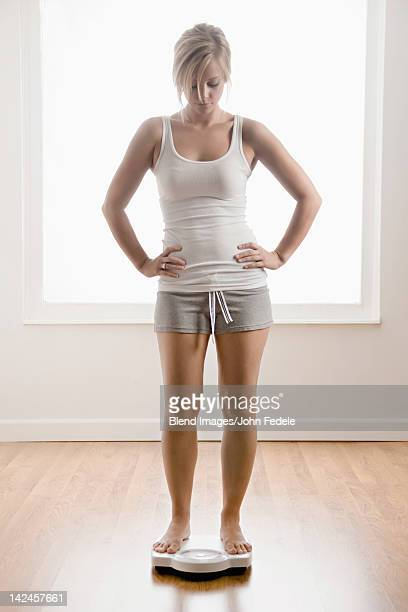 Caucasian woman standing on scale