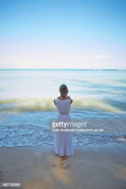 Caucasian woman standing on tropical beach