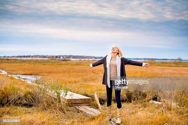 Caucasian woman standing on walkway in rural field