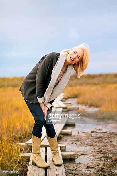Caucasian woman standing on walkway in rural field
