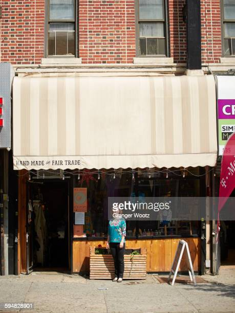 Caucasian woman standing outside store