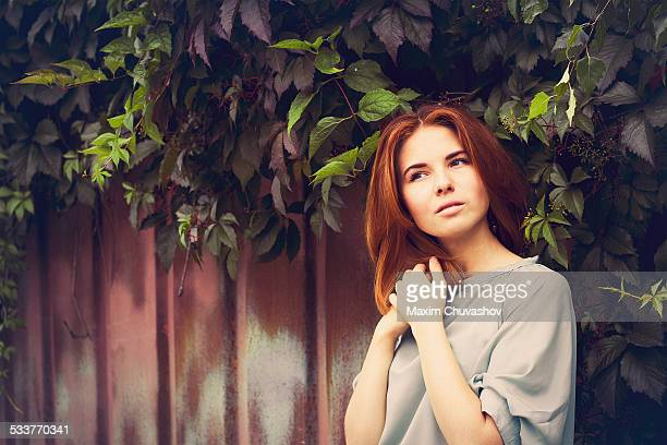 Caucasian woman standing under leaves by fence